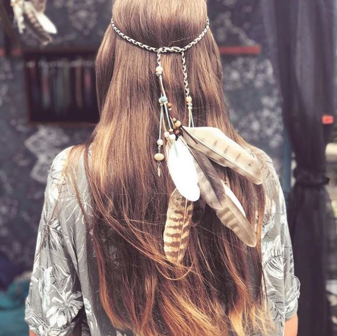 back view of long straight brown hair with hippie inspired headband with dangling feathers