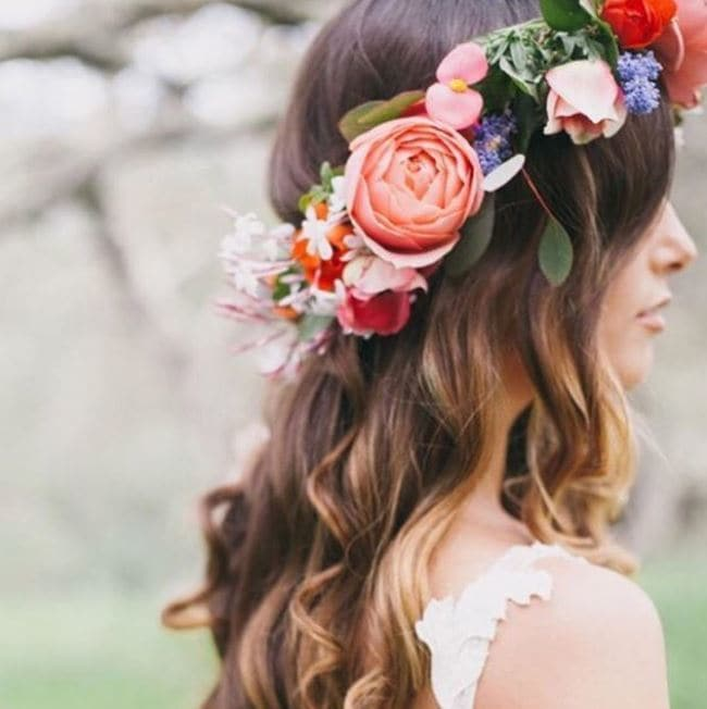 side view of woman with brown wavy hippie hairstyle with flower crown wearing white lace sleeveless dress