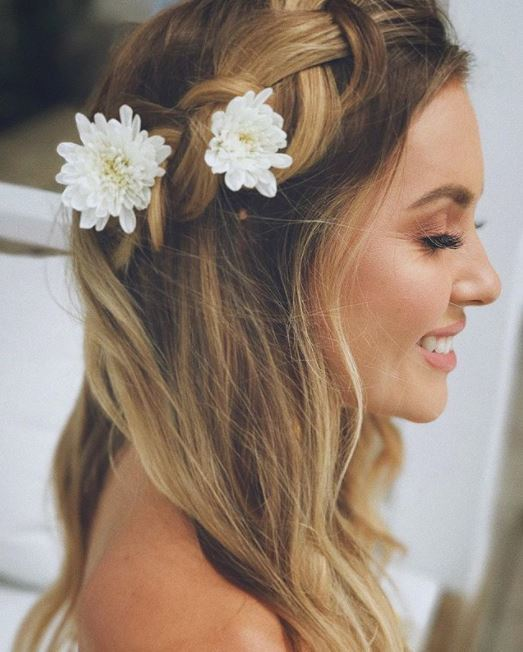 side view of woman with half up crown braid with two white flowers placed in the braid