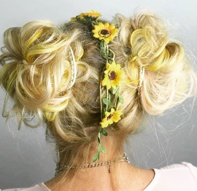 back view of woman with blonde hair in double space buns with sunflowers down the centre parting
