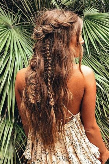 back view of a woman with long wavy tousled hair in half-up rose twist and braided style standing against palm leaves