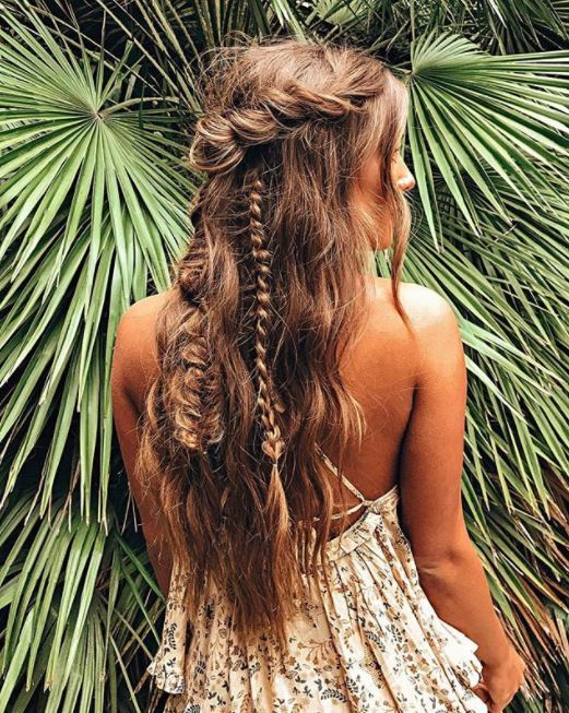 back view of woman with long wavy tousled hair in half-up rose twist and braided style standing against palm leaves