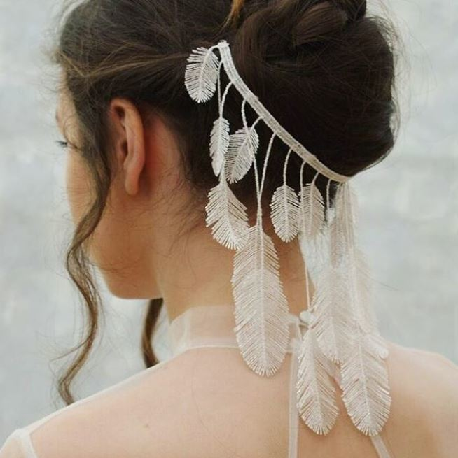 back side view of woman with dark brown hair in updo with white feather hanging detailing wearing sheer white wedding dress