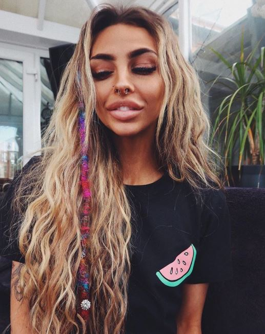 woman with long wavy dirty blonde long hair with multi-coloured single dreadlock