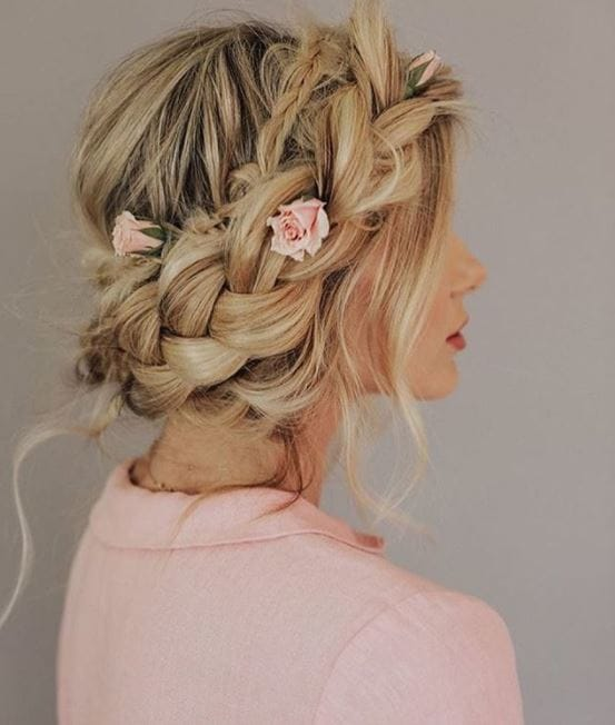 side view of woman with blonde hair in braided crown with small flowers placed throughout wearing light pink top