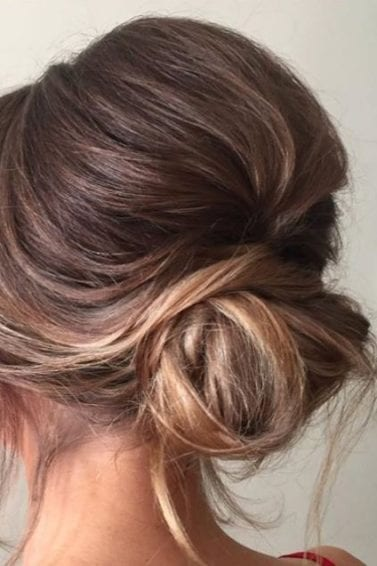 back view of a woman with light brown and dirty blonde straight hair in a low updo with bouffant volume at the crown