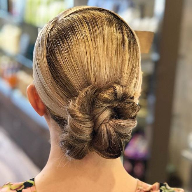 back view of a woman with blonde hair in a low sleek bun updo
