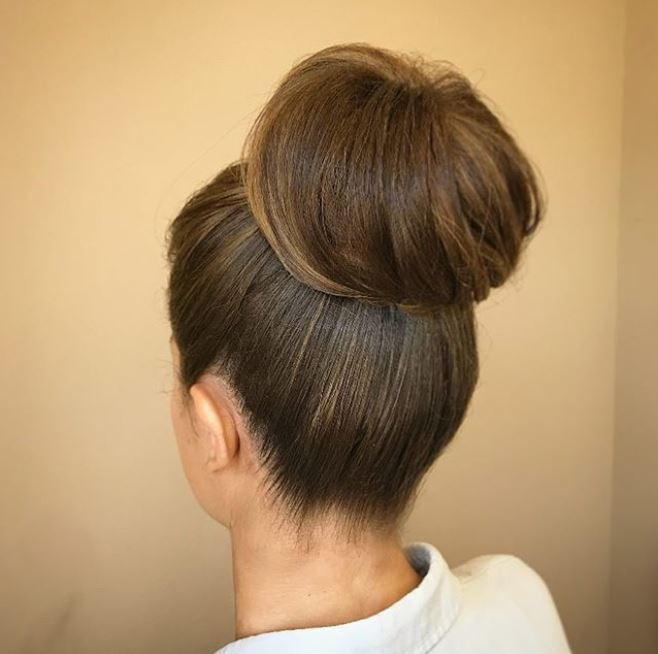 back view of woman with brown hair in high wrapped bun