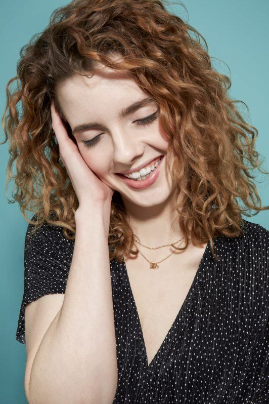 woman with shoulder-length brown-blonde curly hair looking down and smiling with a light blue backdrop