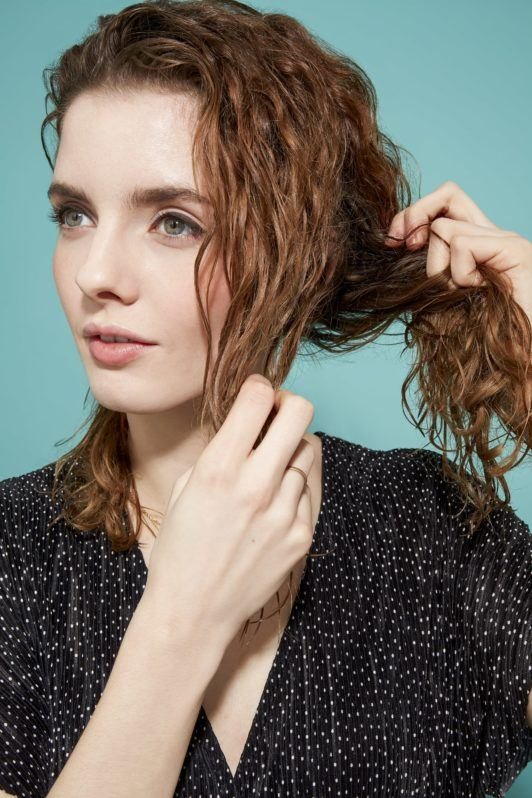 woman with shoulder-length brown-blonde curly hair sectioning off