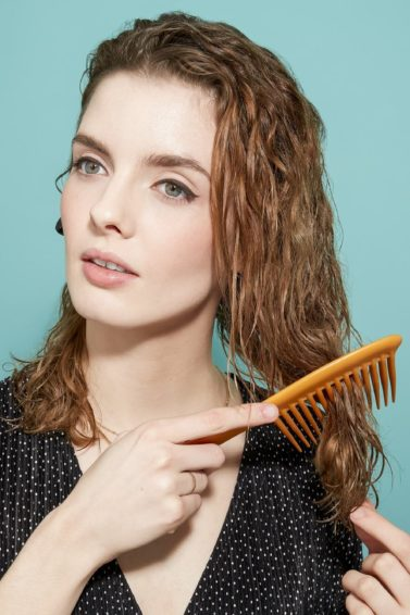 woman with shoulder-length brown-blonde curly hair using a wide tooth comb to gently brush through it
