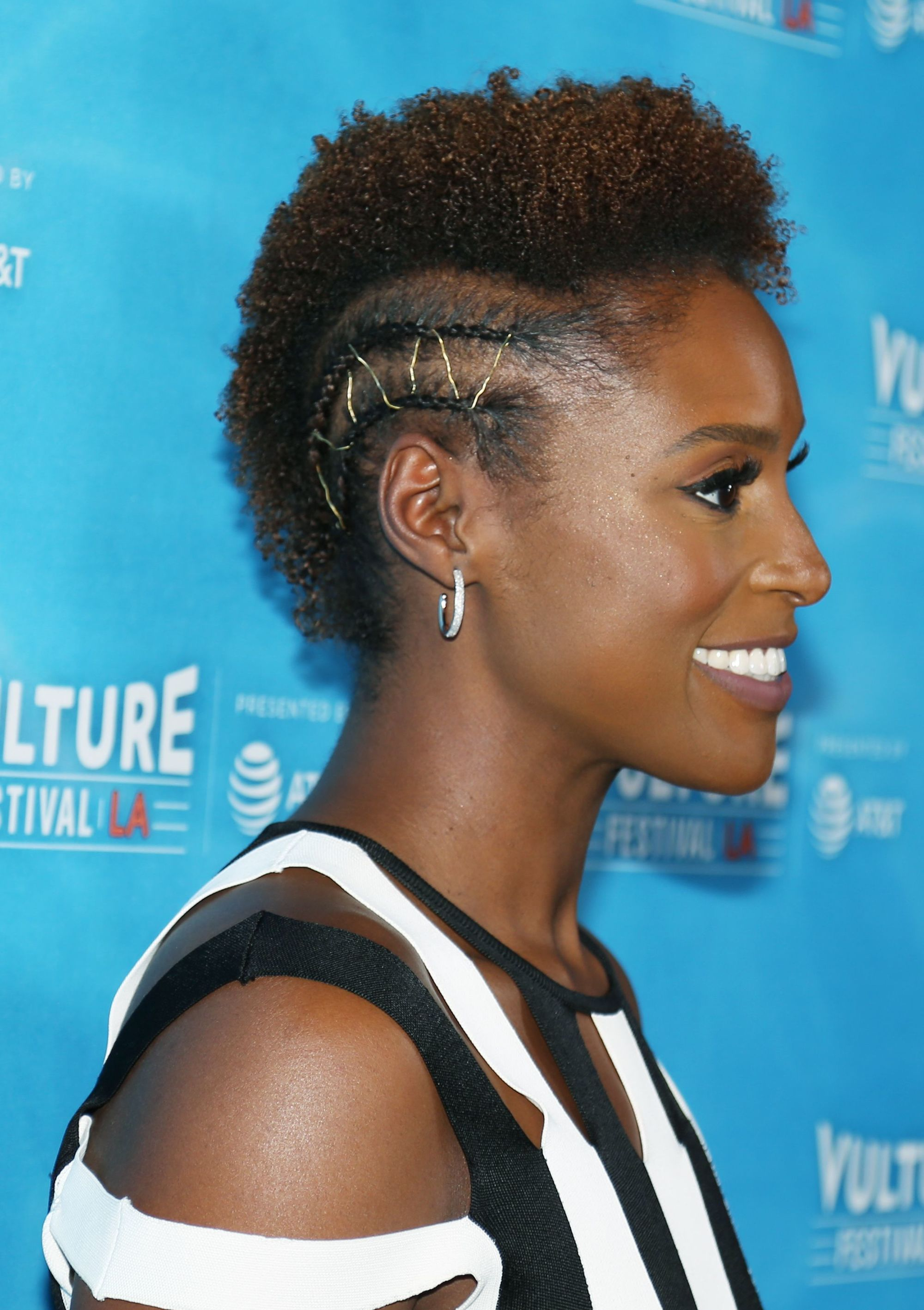 issa rae with an afro mohawk with tiny cornrows either side with metallic golden thread woven through
