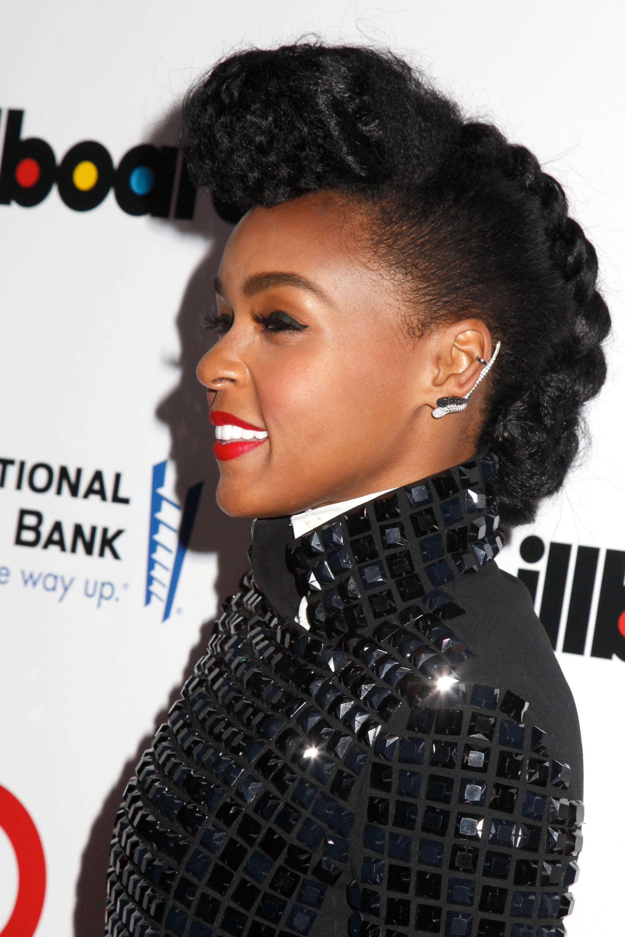 janelle monae on the red carpet wearing a black embellished outfit with her hair styled into a braided mohawk look