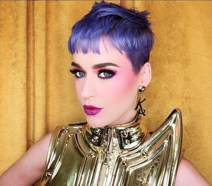 close up shot of katy perry with pastel purple hair,, wearing gold top and posing against gold background