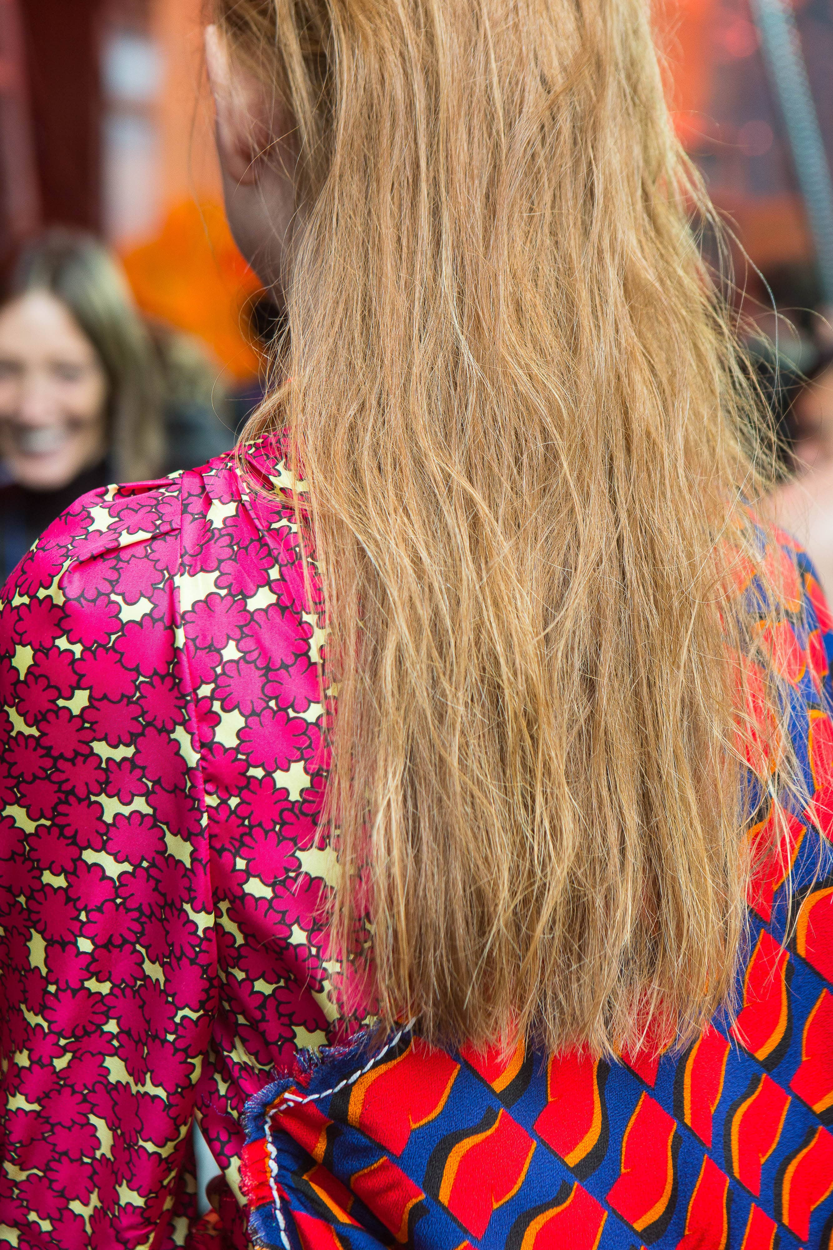 back view of a model with long blonde-brown hair with slight waves, wearing a pink, blue and red patterned outfit