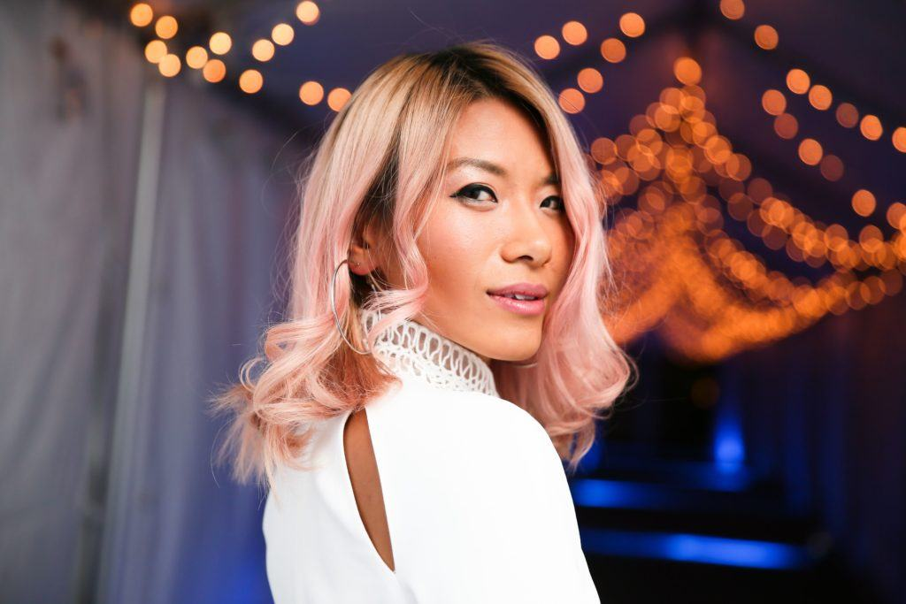 close up shot of May Kowk with rose gold hair, wearing white and posing for picture