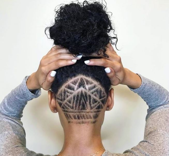 back view of a black woman with dark brown hair in an updo with nape undercut design