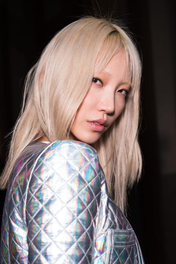 backstage image of a model with platinum blonde hair with bangs parted in the middle, wearing a silver jacket