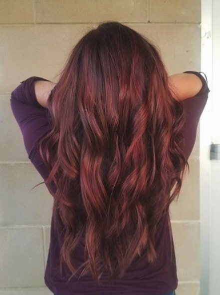 back view of a woman with vibrant long curly cherry hair running her hands through her hair