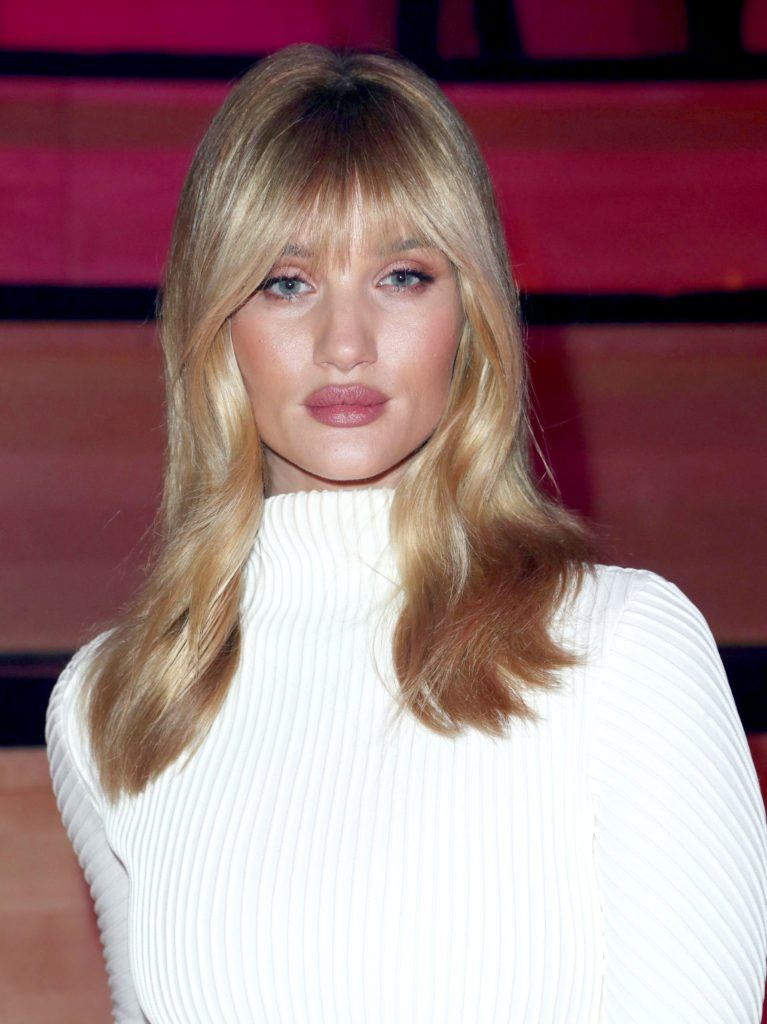 close up shot of Rosie Huntington-Whiteley with blonde hair and wispy bangs, wearing white and posing at a runway show