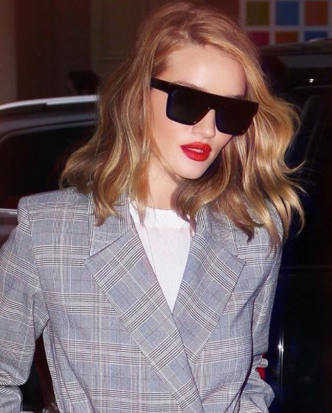 paparazzi shot of rosie huntington whiteley wearing a grey prince of wales check blazer and thick black sunglasses with lob length wavy honey brown hair styled in a center parting