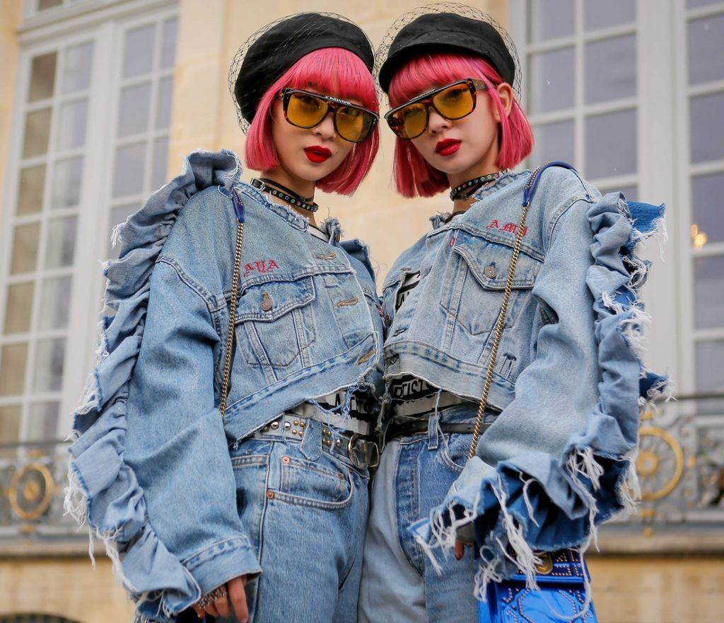 image of two women on the street dressed the same in all denim with pink bob haircuts with bangs, wearing berets and sunglasses