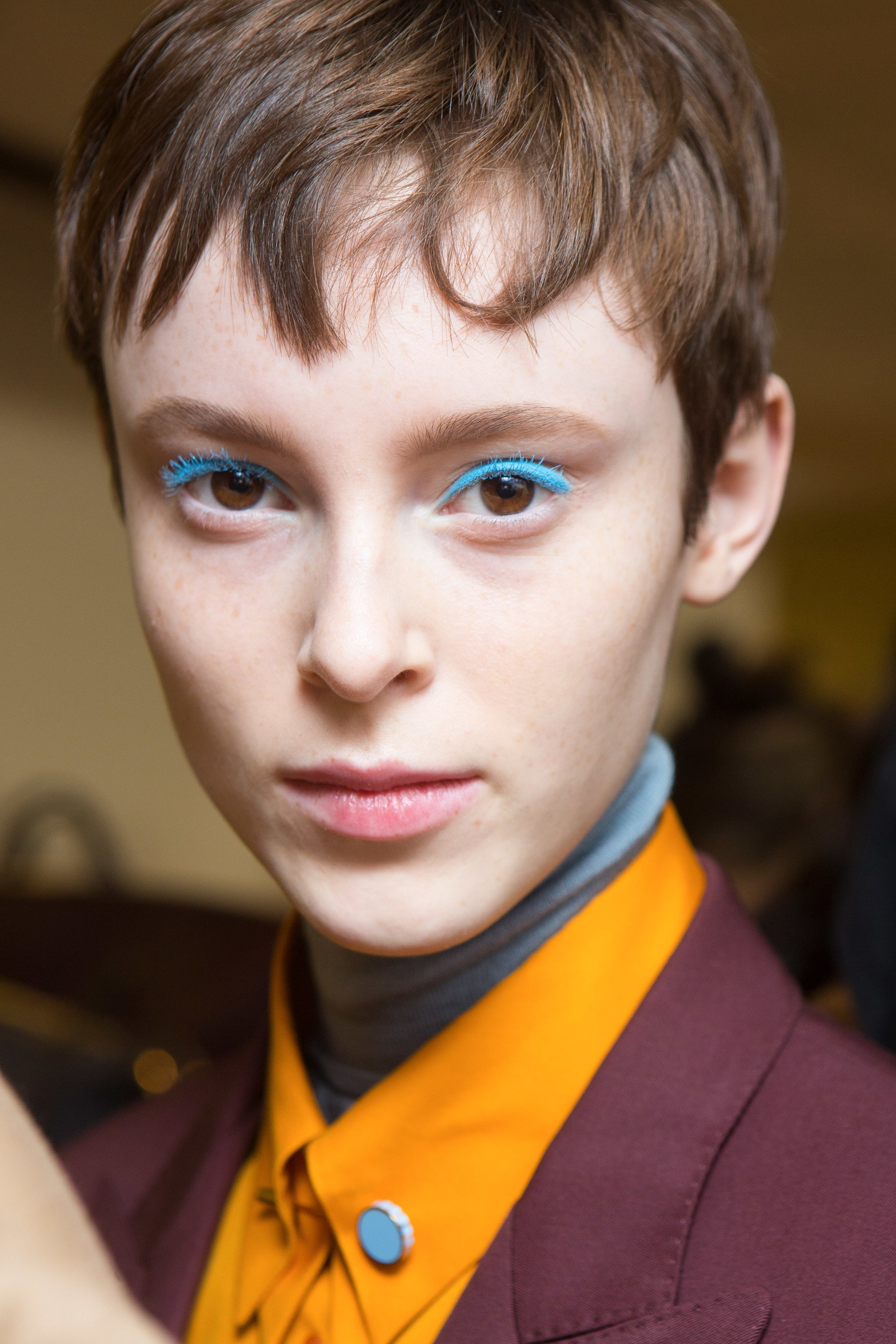 Thinning hair: Close-up shot of a woman with a short brunette pixie cut, wearing bright eye makeup