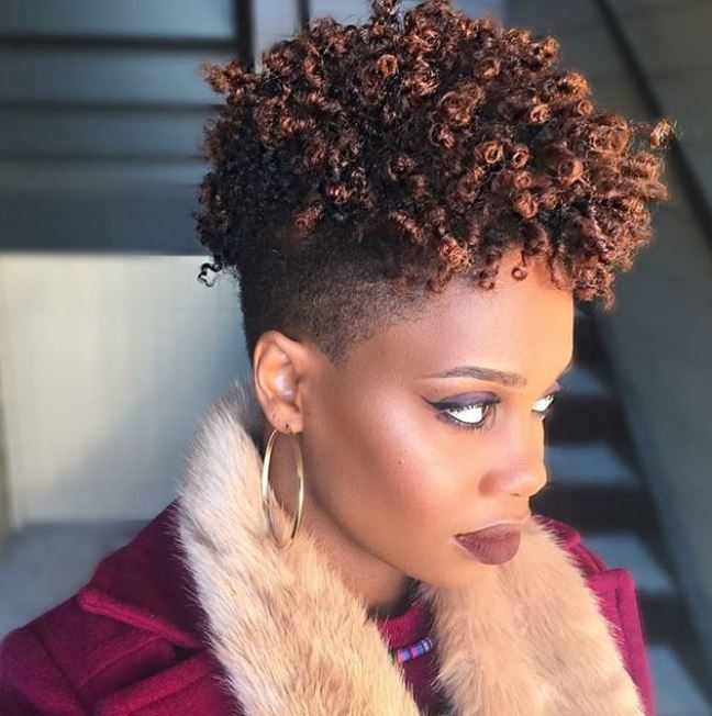 side profile of a black woman with shaved sides and a curly mohawk top in chocolate and caramel brown highlights