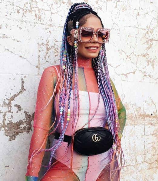 black woman with multi-coloured braids and shaved undercut sides wearing sunglasses
