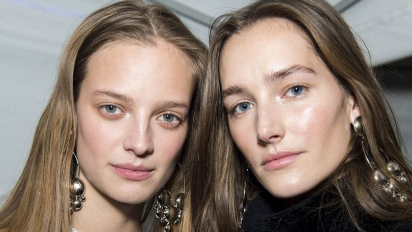 the best flat iron spray: close up shot of two models backstage with sleek, shiny strands, wearing black and white
