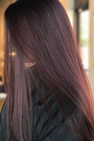side view of a woman with super long straight mahogany hair with a reddish tint