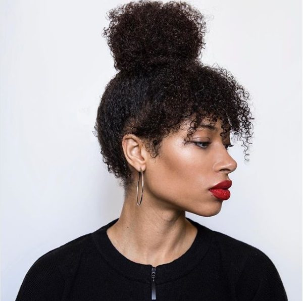 side profile of a woman wearing a black zip up top with her natural hair in a topknot with tinkerbell style bangs