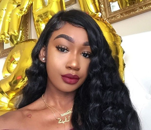 curly weave hairstyles: close up shot of woman with long, hollywood-inspired weave hairstyle with side parting, posing