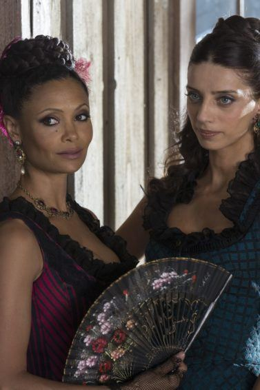 close up shot westworld characters maeve and clementine with a braided updo and half updo hairstyle, wearing costume dresses on set