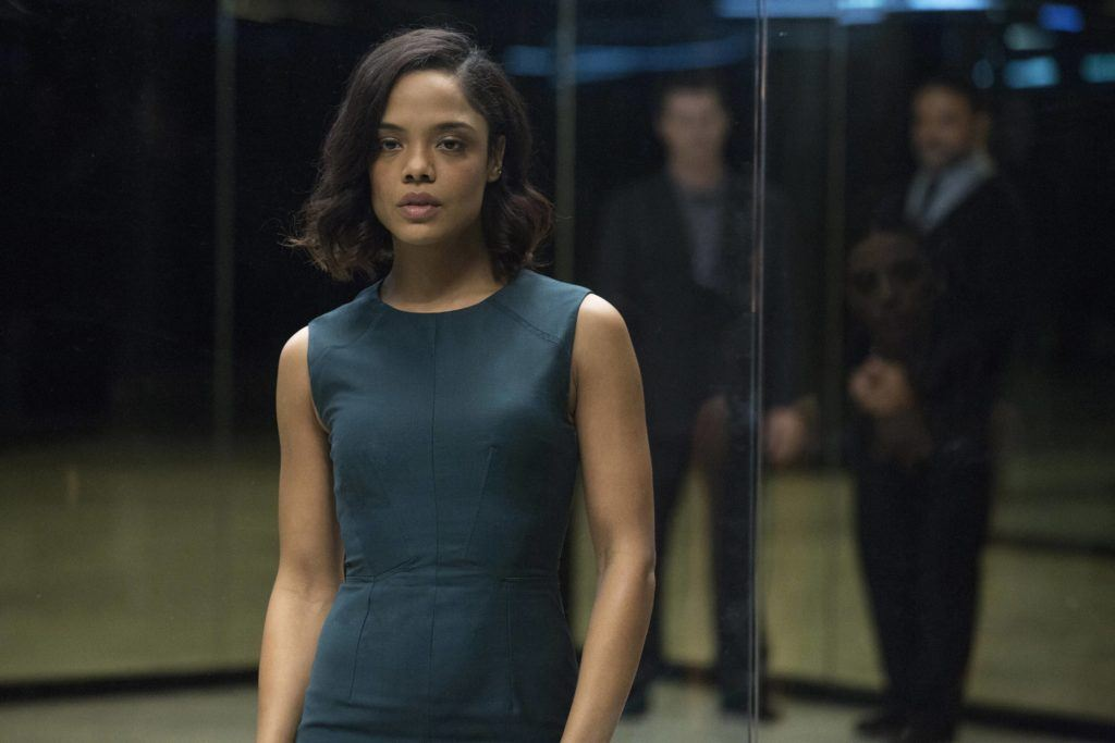 close up shot of tessa thompson as charlotte hale, wearing blue dress with wavy short hair, on the set of westworld
