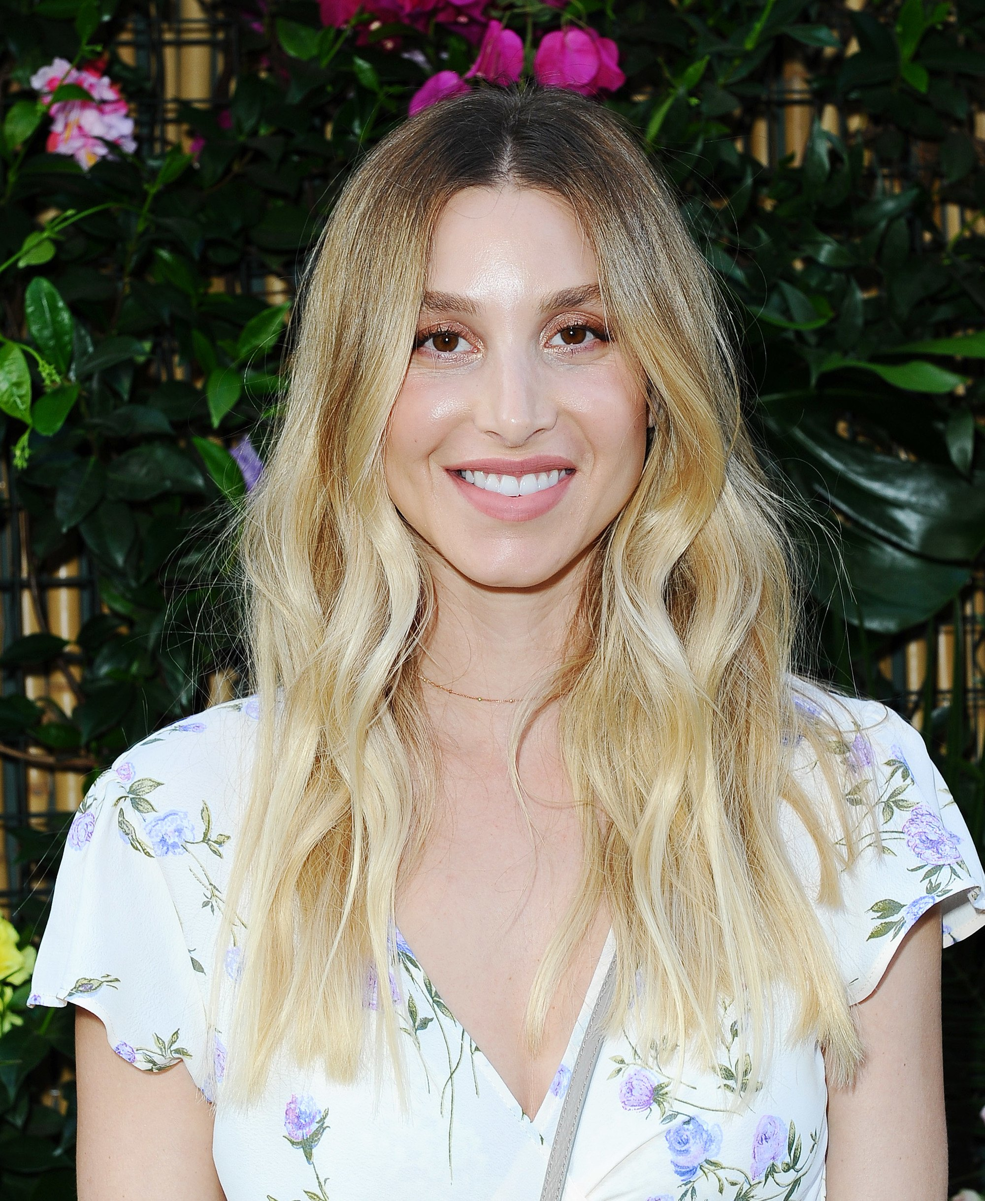 close up shot whitney port with dark to golden blonde ombre hair, wearing floral dress and posing outside at an event