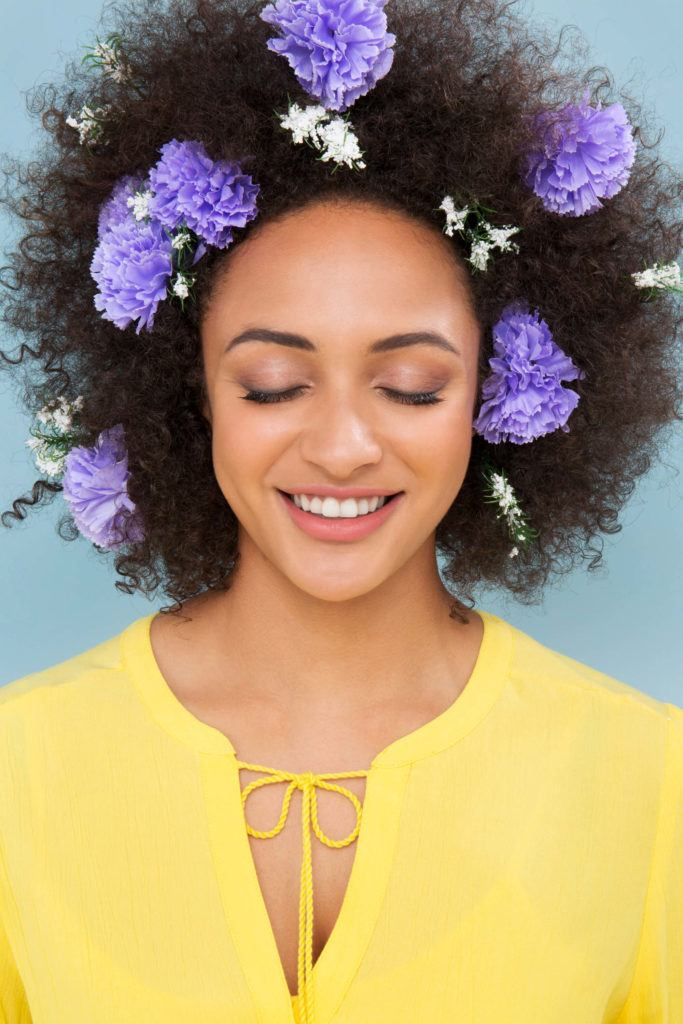 Easy natural hairstyles: Close up shot of woman with fluffed out natural afro hair with flowers in it, wearing yellow dress and posing in studio.