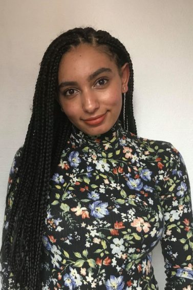 close up shot of model with long box braids swept to the side, wearing floral bodysuit and posing against white background