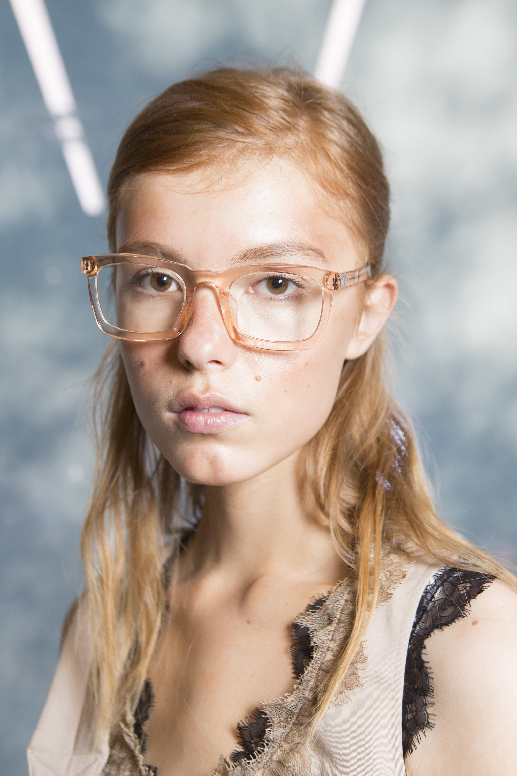 work hairstyles for long hair: model with golden blonde long hair styled in a half-up, half-down side parted style wearing reading glasses