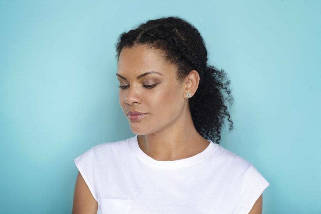 easy natural hairstyles: close up shot of woman with natural braided ponytail, wearing all white and posing in studio