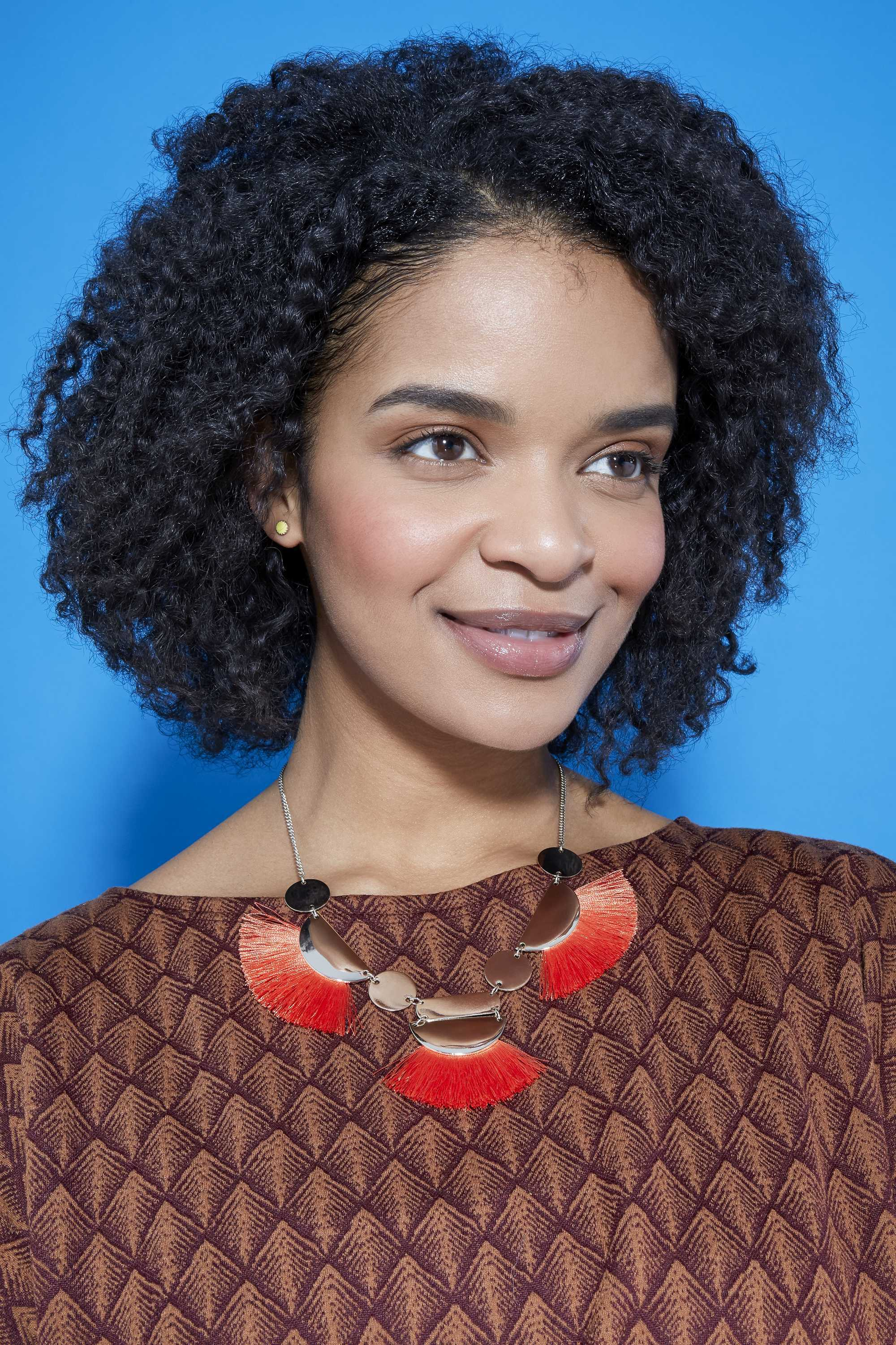 Easy natural hairstyles: Close up shot of woman with braid out hairstyle in studio wearing brown pattern top and red necklace.