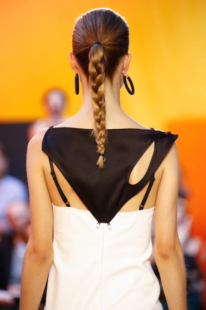 work hairstyles for long hair: back view of a woman with dark blonde long hair styled in a ponytail braid on runway