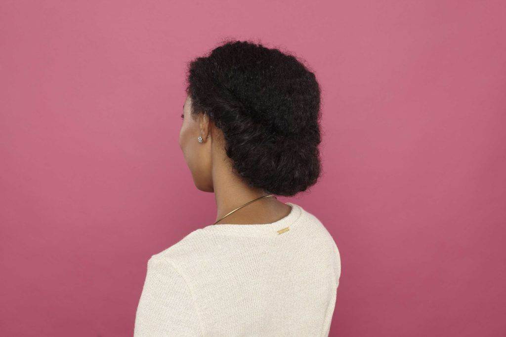Easy natural hairstyles: Close up shot of woman with natural hair styled into a gibson tuck, wearing white and posing in a studio with a pink background.