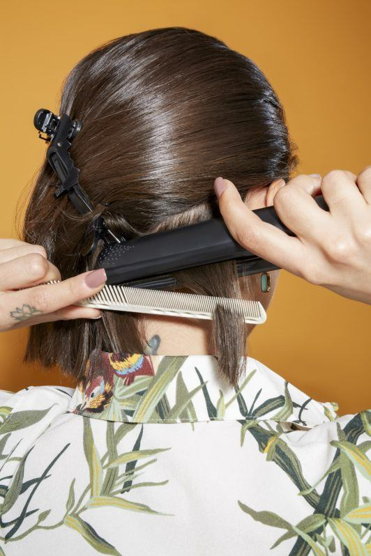 back view of a woman with shoulder length dark brown hair using a straightener and a comb to style her hair