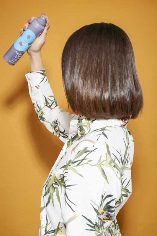 back view of a woman with shoulder length dark brown hair styled straight and curled under spraying hairspray
