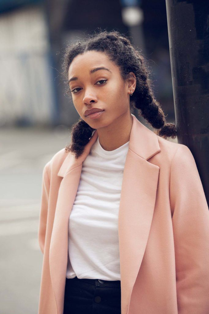 easy natural hairstyles: close up shot of street style model with natural hair styled it into flat twist pigtails, wearing pink jacket with white tee and black jeans