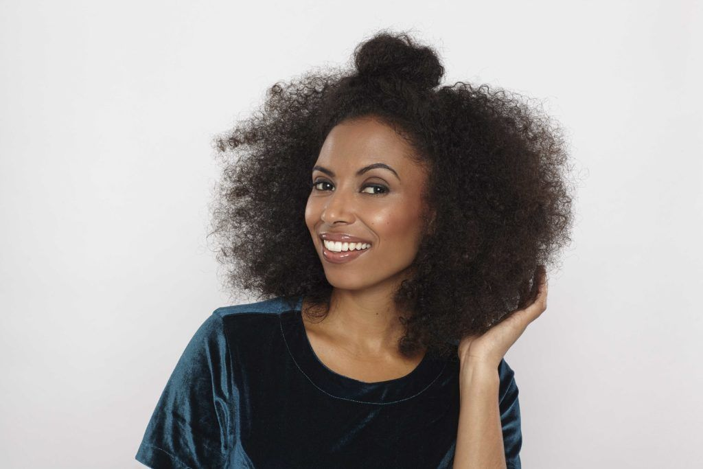 easy natural hairstyles: close up shot of model with natural hair styled into a half up half down bun hairstyle, wearing velvet top and posing in a studio