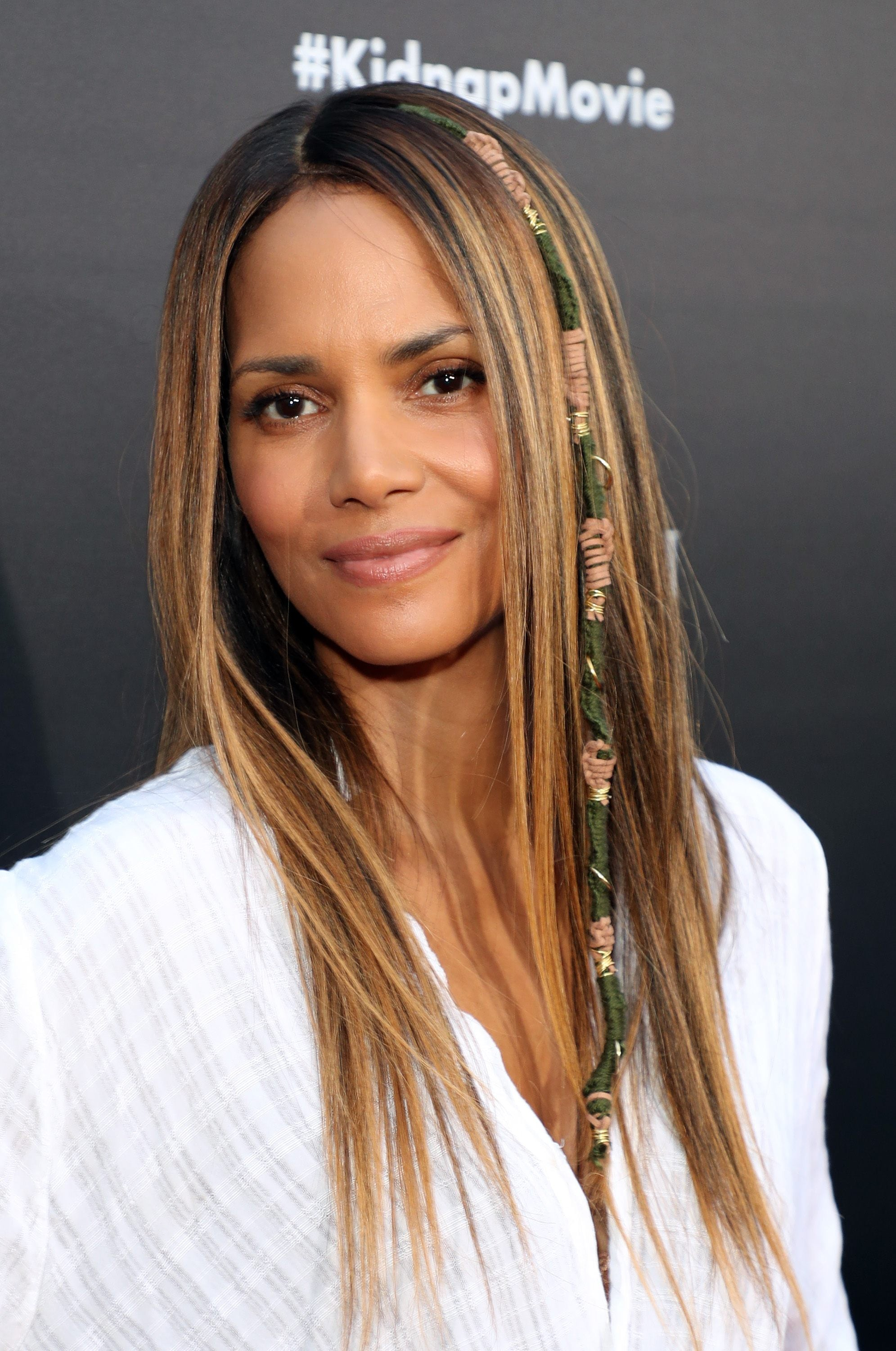 halle berry with straight long light brown hair with darker brunette lowlights and a patterned hair wrap