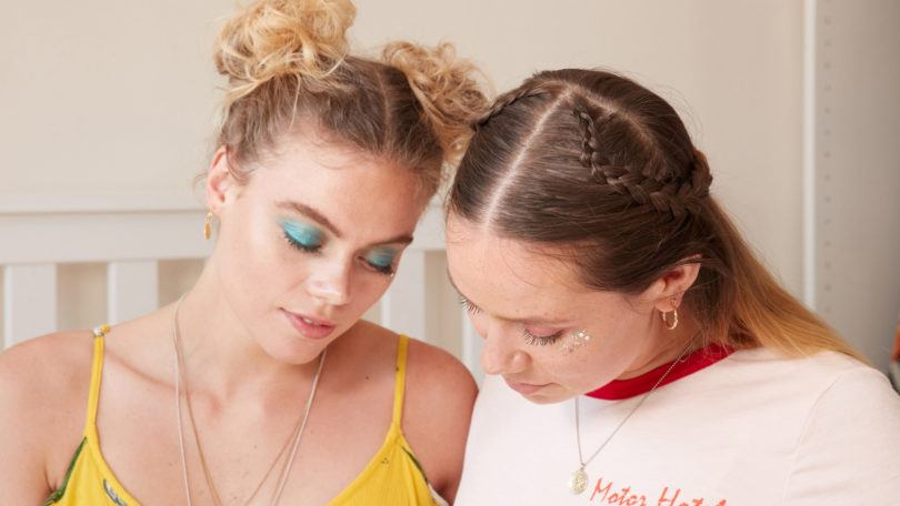 heart braid tutorial: close up shot of two models, one with space buns, the other with a half-up, half-down heart braid, one wearing a white top and the other wearing a yellow sundress