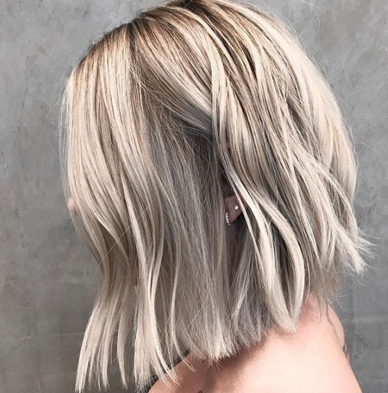 New hair colour trends: Close up shot of a woman with ash blonde and light blonde shadow tone hair.